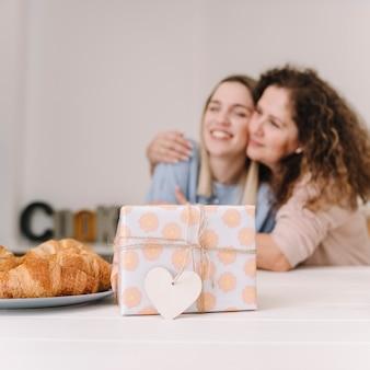 抱擁の母と娘の近くに素敵なプレゼント