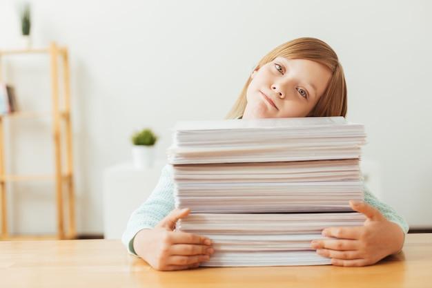 Симпатичная очаровательная девочка с кучей статей, которые ей нужно просмотреть, работая над своим домашним проектом.
