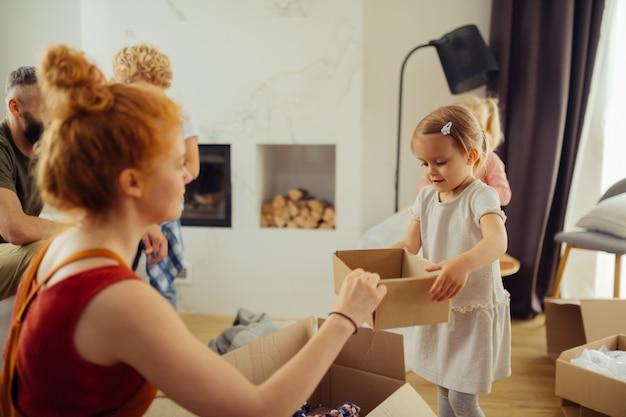 彼女の母親に箱をもたらす素敵なかわいい女の子