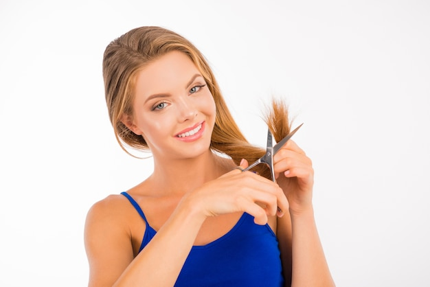 Nice pretty woman cutting her split ends