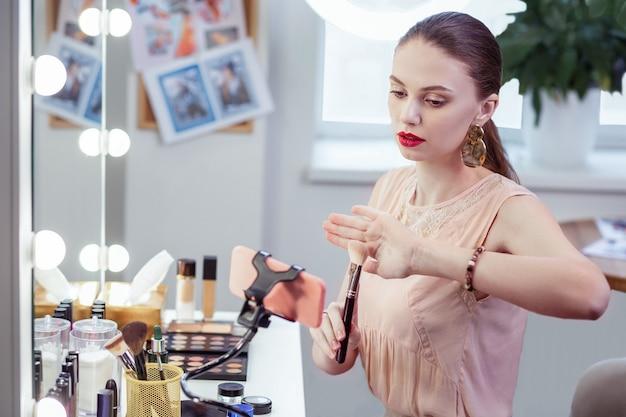 彼女自身のブログを持っている間化粧ブラシについてのアドバイスを与える素敵なきれいな女性