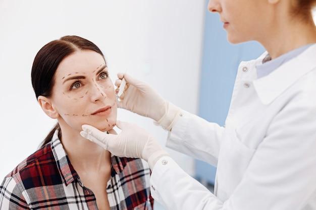 メスを持って患者の前に立ってカットをする準備をしている素敵なプロの美容整形外科医