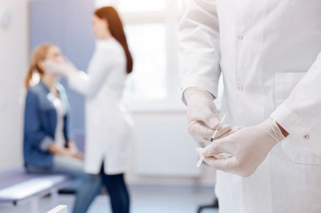 주사기를 들고 테이블 근처에 서있는 동안 주사를 준비하는 좋은 전문 경험이 풍부한 의사