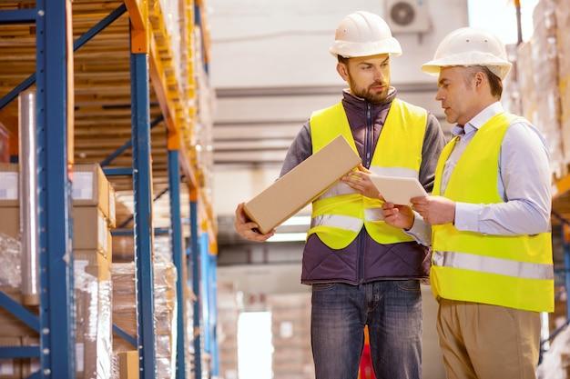 Хороший профессиональный менеджер разговаривает со своим подчиненным, проверяя ящики с товарами
