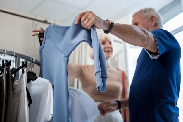 素敵なプルオーバー。ショッピングストアで老夫婦の手に保持されているファッショナブルな高品質のプルオーバーの選択的な焦点