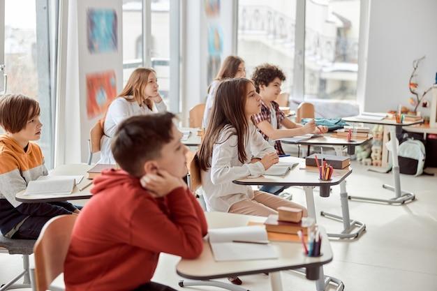 좋은 학생들은 튜터의 말을주의 깊게 듣고 있습니다. 책상에 앉아 교실에서 책을 읽는 초등학교 아이들.