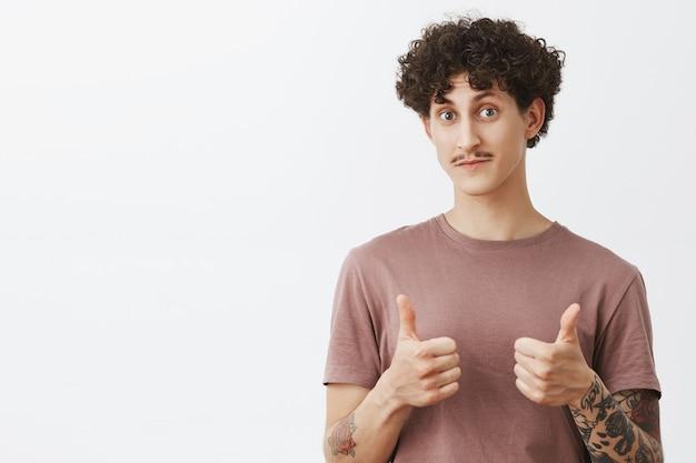 정말 좋아요. 콧수염과 곱슬 헤어 스타일이 눈썹을 올리고 승인 제스처로 고개를 끄덕이는 엄지 손가락을 보여주는 놀랍고 인상적인 멋진 세련된 남성 친구 가지지합니다.