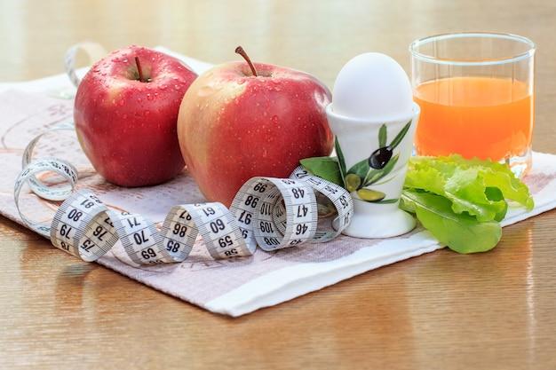 素敵な赤いリンゴ、卵、サラダ、定規、テーブルの上のガラスのマルチビタミンジュース