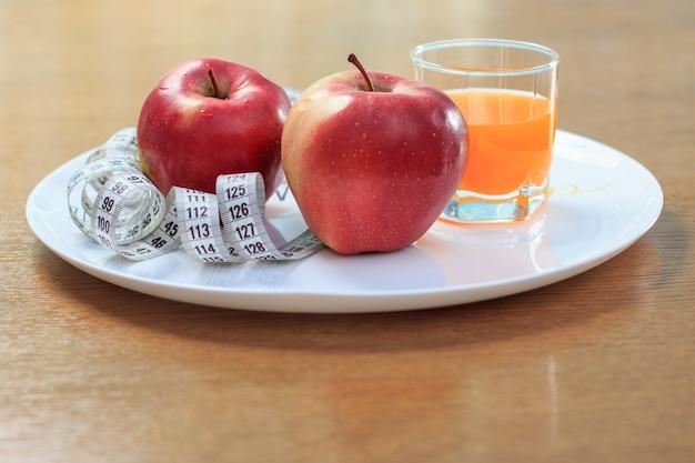 素敵な赤いリンゴ、皿の上の定規、テーブルの上のガラスのマルチビタミンジュース