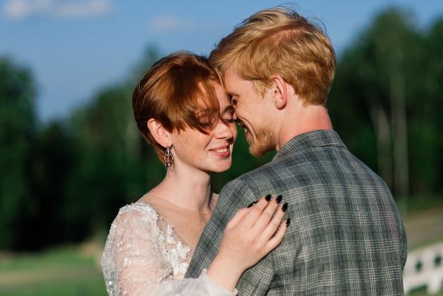素敵な赤毛の若いちょうど結婚している幸せなカップルが夕日の屋外でキス