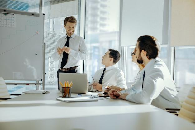 良い結果。ホワイトボードの近くに立ってグラフを描きながら、会社の仕事について同僚に報告する魅力的な明るい青年