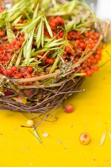 Красивые спелые грозди ягод рябины в плетеной корзине на желтом фоне