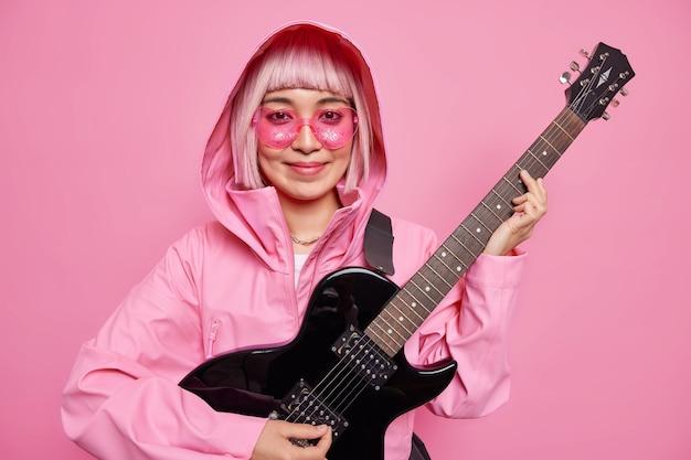 좋은 만족 한 10 대 소녀가 어쿠스틱 기타 드램을 연주하여 유명 가수가되기 위해 핑크색 재킷을 입고 유행하는 선글라스가 실내에서 포즈를 취합니다. 매력적인 여성 솔리스트가 신곡을 연습합니다. 프리미엄 사진