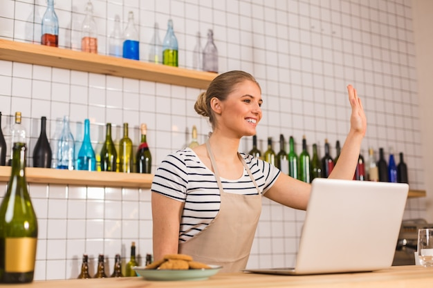 Nice to see you. cheerful nice positive woman standing at the counter and waving her hand while showing hospitality