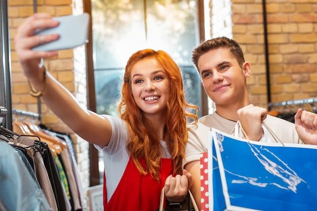 Хорошее селфи. милая расслабленная молодая девушка держит современное устройство и улыбается, делая селфи в магазине одежды со своим любящим парнем