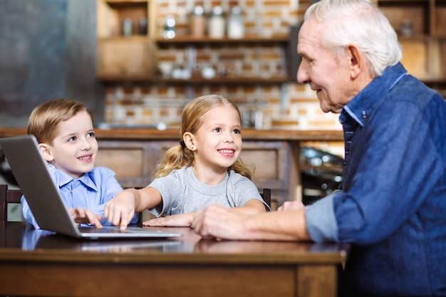 Хороший старший мужчина, используя ноутбук, пока маленькие внуки сидят рядом