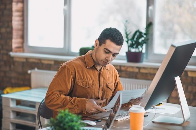 Хороший серьезный мужчина смотрит на документ, сосредоточившись на своем проекте на работе
