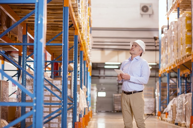 Хороший серьезный мужчина смотрит вверх, проверяя склад на предмет безопасности