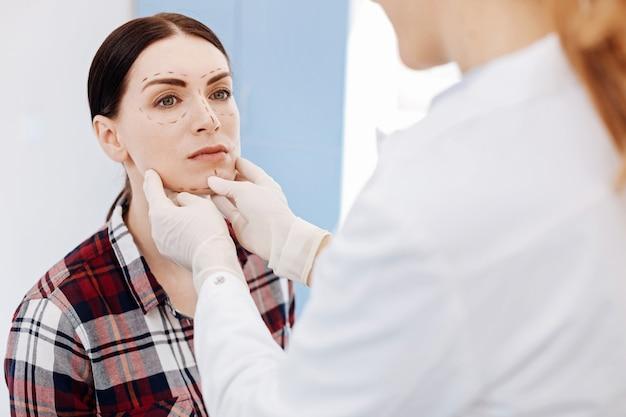 그녀의 의사 앞에 앉아 얼굴 수술을 준비하는 동안 그녀의 얼굴에 교정 라인을 갖는 좋은 심각한 젊은 여자