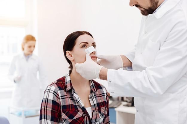 성형 외과 의사 앞에 앉아 코뿔소 플라스틱을하는 동안 그녀의 코에 의료 드레싱을 갖는 좋은 심각한 젊은 여자