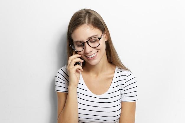 Bella adolescente femminile timida con lunghi capelli sciolti guardando in basso e sorridendo ampiamente mentre parla al telefono cellulare