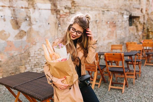 Bella ragazza timida con i capelli lunghi guarda la borsa da forno in piedi nel ristorante all'aperto di fronte al vecchio edificio. signora abbastanza elegante con gli occhiali che raddrizza i capelli e posa dopo la spesa.