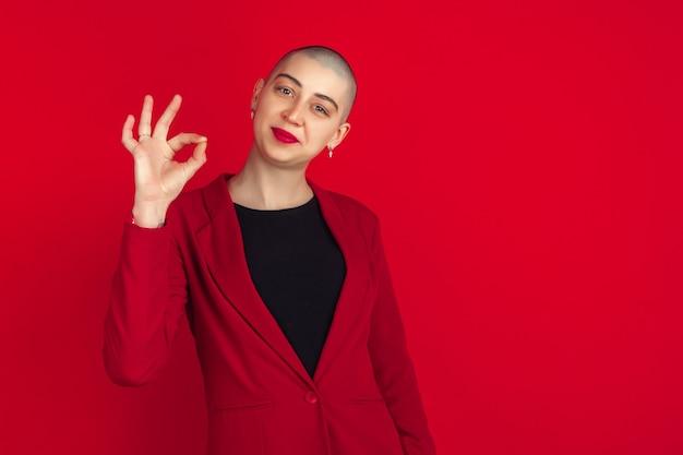 좋은 간판이 보입니다. 빨간 스튜디오 벽에 격리된 젊은 백인 대머리 여성의 초상화.
