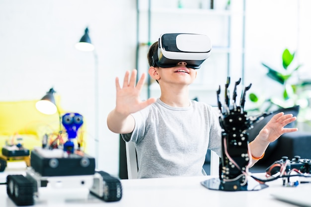 Nice smart enthusiastic boy sitting at the table and wearing vr glasses while experimenting with his robotic devices
