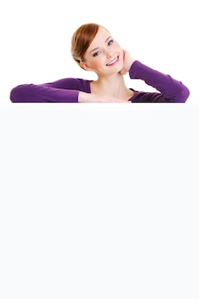 The nice smiling adult female person is over an empty publicity board - on a white space