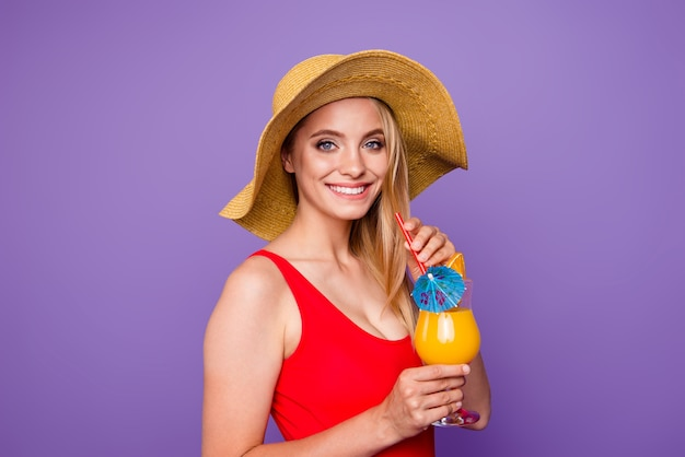 Nice smiling girl wearing red swimsuit sunhat drinking cocktail