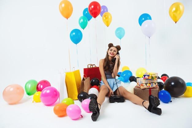 Приятный улыбающийся гриль, получающий телефонные звонки на день рождения во время празднования