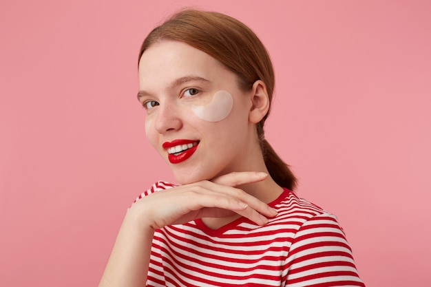 Nice smiling red-haired girl wears in a red striped t-shirt, with red lips and with patches under the eyes, touches the chin, stands and enjoying free time for skin care.