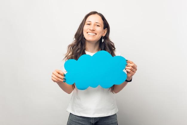 素敵な笑顔の女性は青い紙の雲を保持しています。