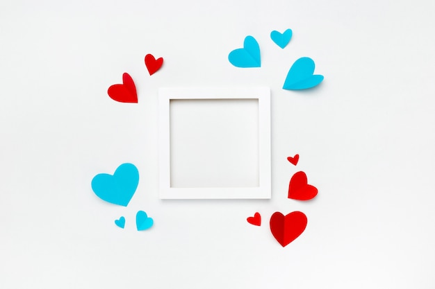 Nice square white frame with copyspace for text on white background decorated with handmade paper hearts