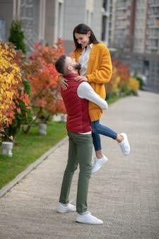 彼女に恋をしている間彼の手で彼のガールフレンドを保持している素敵な強い男