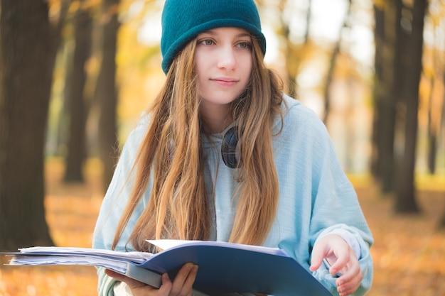自然秋の教科書を読む素敵な学生