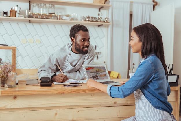 いい提案。同僚の前のカフェカウンターに座って、男性がメモを取りながらウェブサイトのデザインについて話し合っているきれいな女性のバリスタ