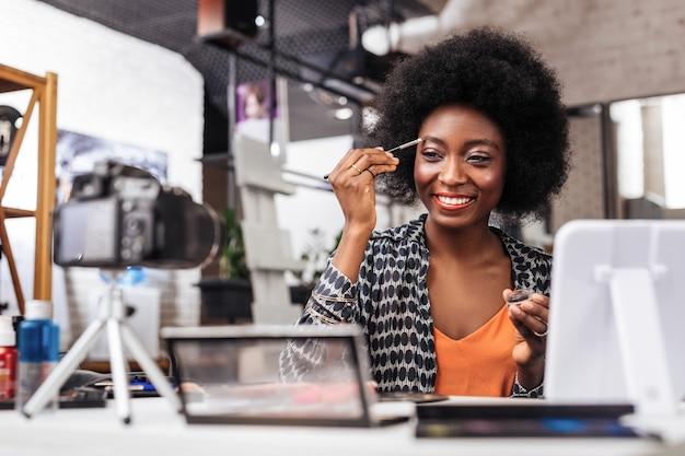 素敵な見本。新しい眉毛の形を試しながら前向きに笑っているオレンジ色のトップで浅黒い肌の女性を笑顔