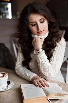 コーヒーを飲む白いドレスの素敵な甘い女の子。パターンで美しく飾られたコーヒー。カフェでラテアートとペストリーで飾られたラテコーヒードリンクのカップ。