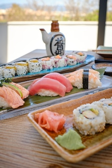 Nice table in asian restaurant with different dishes with sushi pieces.