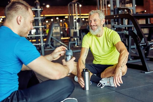 Nice talk after workout cheerful middle aged man in sportswear holding bottle of water and talking