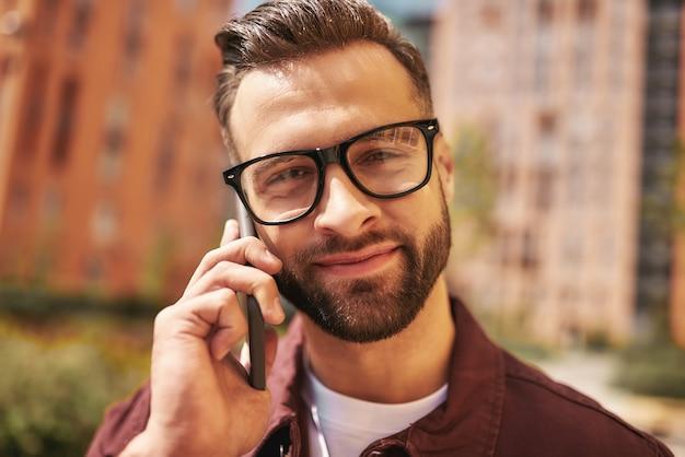 友達といい話。カジュアルな服装と眼鏡で幸せなひげを生やした男の肖像画をクローズアップ電話で話し、通りに立っている間笑顔。ライフスタイル。デジタル。コミュニケーション