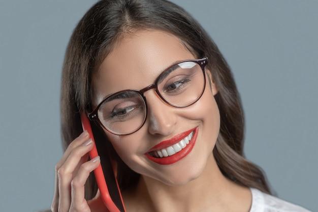 楽しい会話でした。スマートフォンで話している白い歯の笑顔で彼女の唇に赤い口紅とメガネの美しい若い女性のクローズアップ
