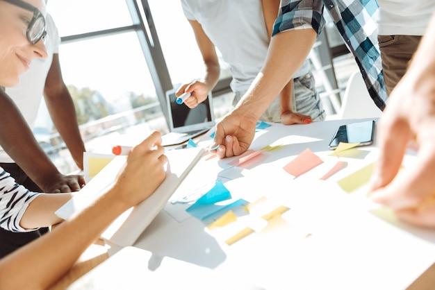 Хорошая командная работа. крупный план группы людей, работающих вместе над проектом и использующих стикеры, обдумывая свои идеи.