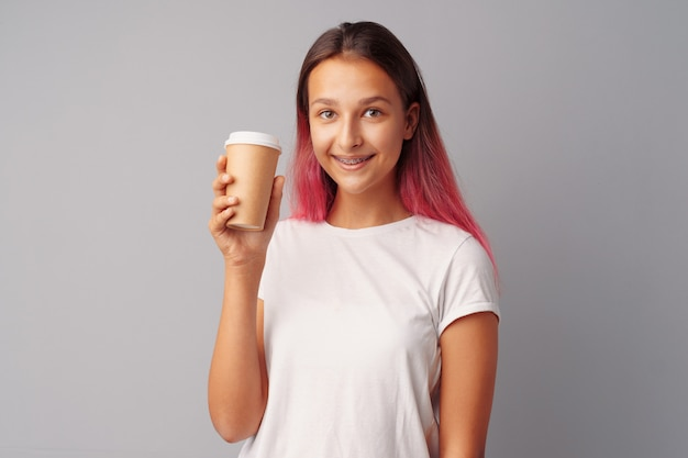 Nice teenager girl holding a cup of coffee over a gray