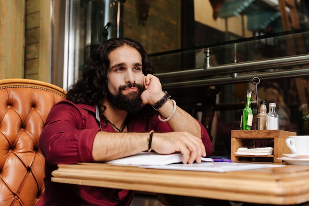Хороший вдумчивый мужчина в кафе, думая о своей работе