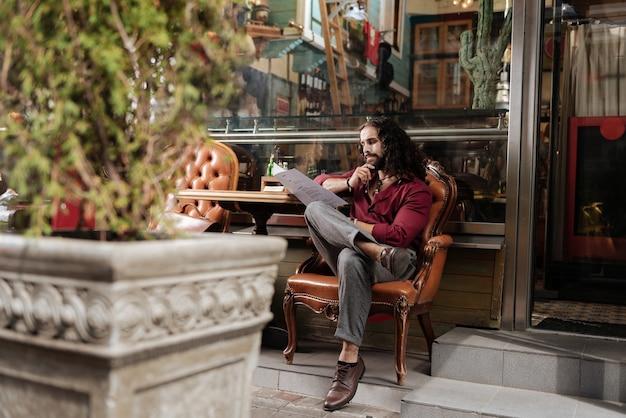 Симпатичный вдумчивый мужчина держит меню, выбирая блюдо в ресторане