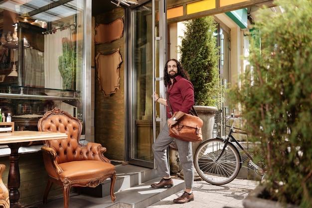 Хороший вдумчивый мужчина стоит у двери при входе в кафе