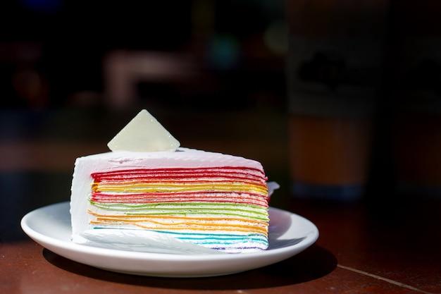 하얀 접시에 로고에 대 한 빈 설탕 시트와 레인 보우 크레페 케이크를 먹고 좋은