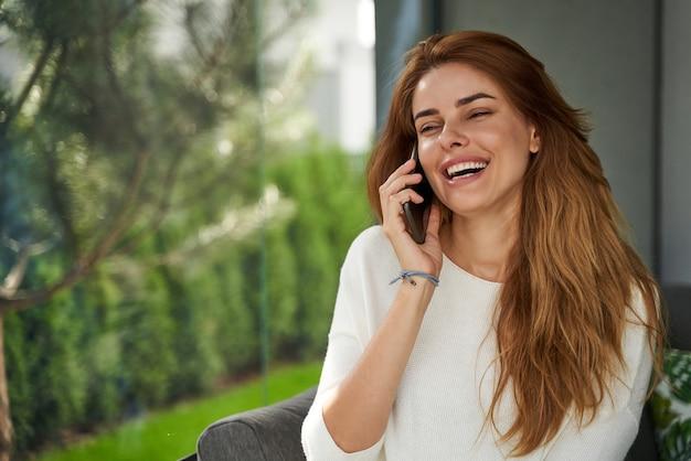 반갑습니다. 그녀의 테라스에 서서 누군가와 전화 통화를 하는 쾌활한 노년 여성의 허리 위로 초상화. 스톡 사진